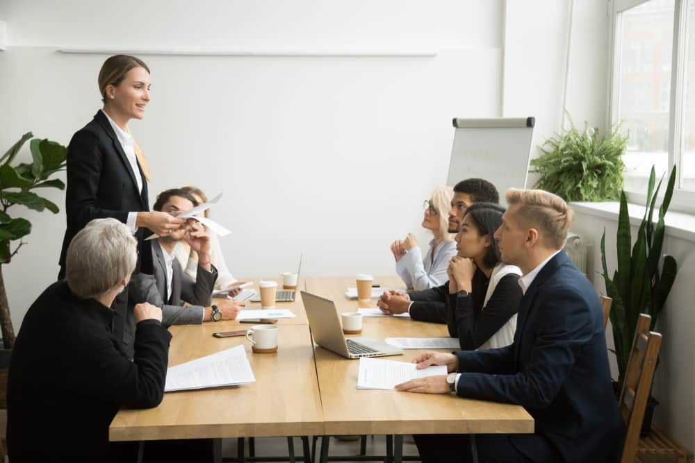 Successful female boss leading team meeting talking to multiracial employees, woman executive leader discussing work results presenting contract report to diverse partners at company group briefing